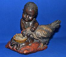 VICTORIAN CHALK SCULPTURE   Victorian polychrome child sculpture of negre baby feeding chicken.  11 1/2'' hieght.  No Mark. Condition age appropriate wear.