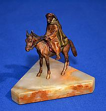 SMALL AUSTRIAN STYLE BRONZE (?) SCULPTURE   Small cold painted sculpture of Arab on horseback.  Set on shaped triangular onyx base.  3 1/2'' hieght.  3 x 3 1/4'' base.  No Mark. Condition age appropriate wear.  Sculpture loose at base.