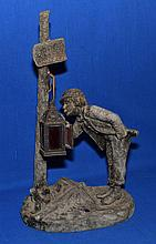 FRENCH SPELTAR LAMP BASE French figural lamp base. Miner uses hanging lantern to light a cigarette. Plaque marked ''Rue Barree''. 16'' hieght. 9 1/2'' wide. 5 1/2'' deep. No Mark. Condition age appropriate wear. Worn metal finish. Missing electrical