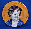 ITALIAN FAIENCE SAINT'S HEAD   Italian faience wall plaque. Head of child in a golden halo.  10 1/4'' diam.  4 1/2'' deep.  No Mark. Condition age appropriate wear.  Old repairs.