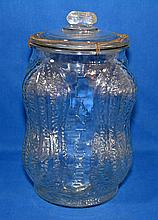 PLANTER PEANUT CONTAINER  Clear molded glass Planters Peanut Container.  Glass lid with wire closure.  Peanut form lid finial. 14'' hieght.  7'' diam.top.  Mark on bottom. Made in USA.  Condition age appropriate wear. Wire closure rusted.