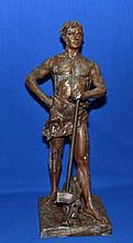 SPELTER FIGURE OF LABOR   Bronze colored spelter figure symbolizing labor with gear and mallet.  18 3/4'' hieght.  6 1/2'' x 6 1/2'' base.  No Mark. Condition age appropriate wear.  Worn finish.
