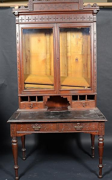 EASTLAKE SECRETARY DESK (Circa 1880's) Incised decoration. Shaped cornice, two glass doors, wood shalves, lower section with slanted writing surface, two drawers, turned legs. Condition: old finish, some losses, scuffs and wear.