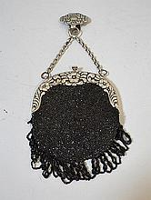 VINTAGE BEADED EVENING BAG. black glass bead encrusted evening bag, black bead fringe with floral and scroll silver repousse frame, chain with belt hook. No mark. Size; 6''H, 5''W. 8''Chain, 1 1/2''H belt hook. Condition: age appropriate wear.