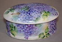 OVAL HAND PAINTED PORCELAIN CONTAINER  Oval lidded container. Painted on exterior and interior Purple/Blue Lilacs.  4'H. 7 1/4''L. 5 1/2''W.  No Mark. Condition, age appropriate wear.