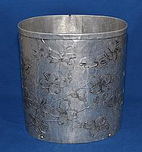 WENDELL AUGUST FORGE DOGWOOD PATTERN WASTE BASKET  Oval form aluminum waste basket. 10''H. 9 1/2''L. 7 1/4''diam.  Mark, Wendell August FOrge Hand Made Grove City PA.  Condition, age appropriate wear. (dents on bottom rim).