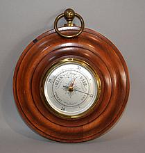 HOWARD MILLER WALL BAROMETER Wall mount barometer with wide wood frame. Brass ring hanger top. 10''diam. 3 1/2''H. ring hanger. Mark, Howard Miller Clock Co. Zealand, Michigan USA. Condition, age appropriate wear. All clocks and mechanical devices