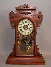 VICTORIAN WALNUT CLOCK   Victorian keywind, pendulum driven. Half hour strike walnut eastlake style clock. Stenciled clock window.  21 1/4''H. 14''W.base. 5''D.base.  No Mark. Condition, age appropriate wear. All clocks sold as is.