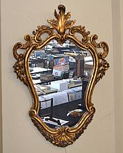 GESSOED WALL MIRROR  Gilt gessoed wall mirror. Shield form with ''c'' scroll, rosette and swag decoration. 31''H. 21''W. No Mark. Condition, age appropriate wear. (minor loss to gesso/glue repair upper right ornament).