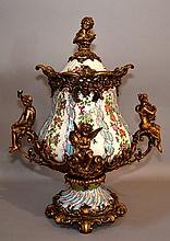 FRENCH LIDDED URN French style metal and ceramic lidded urn. Rococo style metal framework with putti and female figures. Ceramic body with polychrome ribbon and flower garland decoration. 20''H. 15 1/2''W.at handles. Mark, Crown&Shield; Cartouche.