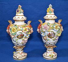 PAIR DRESDEN PORCELAIN LIDDED COMPOTES Pair polychrome floral decorated porcelain lidded compotes. Each with face and shell form handles. One side with hand painted floral cartouches. One side with decaled 18th.c. genre scene. 9 1/2''H. 4