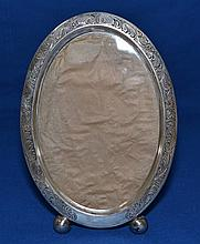 WILLIAM B. KERR STERLING PICTURE FRAME  Oval sterling picture frame. Raised on 2 bull feet and engraved scroll and floral decoration. Easel back. 7''H. 5 1/2''W. Mark, William B. Kerr & Co. Sterling 2845E. Condition, age appropriate wear.