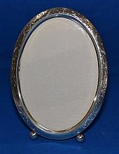 WILLIAM B. KERR STERLING PICTURE FRAME  Oval sterling frame. Raised on 2 bull feet. Engraved scroll and flower decoration. Easel back. 8''H. 6''W. Mark, William B. Kerr & Co. Hallmark Sterling 2848E. Condition, age appropriate wear.
