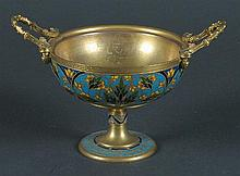 FRENCH CHAMPLEVE ENAMEL COMPOTE. Footed form with two handles, polychrome champleve floral and scroll decoration. Marked: top rim inscribed: F. Barbedienne. Bottom marked: ''R''. Size: 4 1/4''H, 4 1/2''Diam. top, 2 1/2''Diam. base. Condition: age