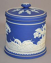 JASPERWARE HUMIDOR/LIDDED CONTAINER Dark Blue and White Jasperware Humidor or Lidded Container. Body decorated with continuous hunting scene. Lid with neoclassical leaf decoration. 5 1/2''H. 4 5/8''diam.base. Mark, inscribed ''3100'' Condition, age