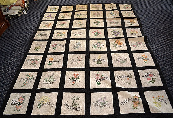 VINTAGE STATE FLOWER QUILT. vintage hand made quilt, white ground with black borders, white backing, 48 white blocks with embroidered banderole with state name, embroidered state flower. No mark. Size; 94''L, 64W. Condition: age appropriate wear.
