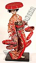 JAPANESE NINYO DOLL. Japanese Ninyo doll, geisha in kimono with numerous hats, set on wooden base. No mark. Size: 17''H, 7'' x 6'' base. Condition: age appropriate wear, dusty.