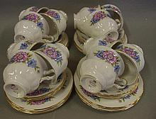 Twelve Queen Anne cup, saucer & plate sets with carnation flower decoration