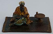 An Austrian cold painted bronze group, modelled as a Moor seated on a patte
