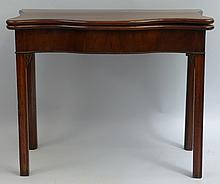A George III mahogany games table, the fold over serpentine top with cross