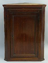 A 19th Century oak corner cupboard, having slightly flared cornice over a s