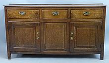 An early 19th Century oak enclosed dresser, having moulded edged top over t