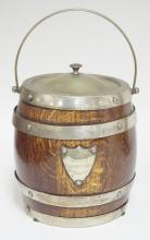 PORCELAIN LINED OAK BISCUIT BARREL W/  SILVER PLATED BINDINGS AND TOP. HAS A SHIELD FORM PLAQUE READING *1927 WORLD CHAMPION NY YANKEES*. 7 1/4 IN H EXCLUDING HANDLE.