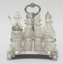 8 MATCHING CUT BOTTLE CASTOR SET W/LONDON STERLING SILVER CENTER HANDLED BOTTLE HOLDER; *CA 1831 EDWARD, EDW JR, JOHN & WILLIAM BERNARD*; 1 BOTTLE HAS CRACK IN NECK & REPLACED STOPPER*; 8 1/2 IN X 7 IN BASE, 9 IN HIGH