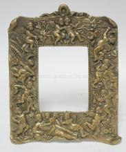 BRONZE PICTURE FRAME WITH CHERUB FIGURES IN RELIEF. 8 1/2 X 10 IN.