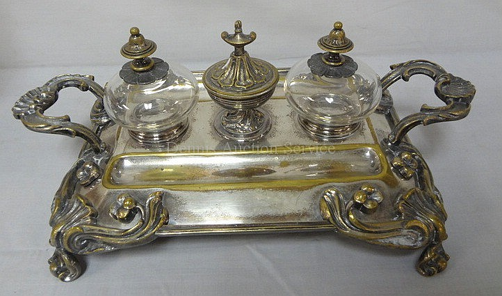 SILVER PLATED DOUBLE INKWELL W/RELIEF FLOWER & SHELL DESIGN; HAS A CENTER STAMP BOX; 14 3/4 IN X 9 1/2 IN