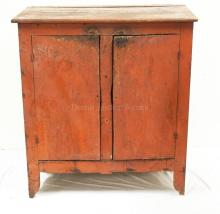 PRIMITIVE 19TH C 2 DOOR CUPBOARD IN RED PAINT. 40 INCHES WIDE. 43 3/4 INCHES HIGH.