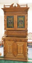 CARVED OAK SIDEBOARD WITH A LEADED GLASS DOOR TOP. CARVED WITH LION HEADS, URNS WITH FLOWERS, ETC. 48 1/2 INCHES WIDE. 97 INCHES HIGH. ONE OF THE GLASS PANELS HAS A HOLE.