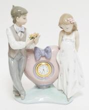 LLADRO PORCELAIN FIGURE OF A COUPLE WITH A HEART SHAPED CLOCK IN THE CENTER. 9 1/2 INCHES HIGH. SOME MISSING FLOWER PETALS.