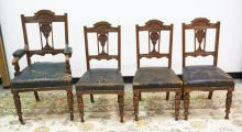 SET OF 5 CARVED OAK CHAIRS. 1 ARM CHAIR AND 4 SIDE CHAIRS. LEATHER SEATS ARE WORN. ARMCHAIR MEASURES 23 1/2 INCHES WIDE AND 43 INCHES HIGH.