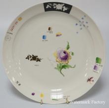 NYMPHENBURG HAND PAINTED SAMPLE PLATE DECORATED WITH A FLOWER. CONTAINS THE NUMBER 2604/134, THE COLOR SWATCHES FOR THE DÉCOR, PATTERN SILHOUETTE, ETC.  10 5/8 INCH DIA.