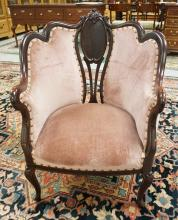 CARVED AND UPHOLSTERED PARLOR CHAIR. HAS SOME REPAIRS.