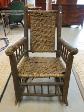 ADIRONDACK ROCKING CHAIR WITH A WOVEN SPLINT SEAT AND BACK.
