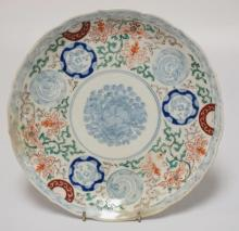 ASIAN PORCELAIN PLATE WITH A FOO DOG CENTER. HAS A REPAIR TO THE RIM. 10 1/8 INCH DIA.