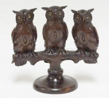 CARVED FRATERNAL *ORDER OF OWLS* WOODEN FIGURE. 3 OWLS PERCHED ON A BRANCH EACH WITH AN *O* ON THEIR CHEST. OWLS HAVE GLASS EYES. 3 EARS ARE DAMAGED OR REPAIRED & 2 TOES CHIPPED. 10 IN TALL.