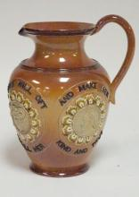 DOULTON BURSLEM PITCHER WITH 4 MEDALLIONS AND THE SAYING *TAKE A FORTUNE AS YOU FIND HER, AND IF SHE FROWN DON'T YOU. A SMILE WITH OFT RECALL HER, AND MAKE HER KIND AND TRUE*. 7 7/8 IN TALL.