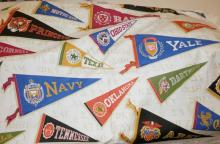 LARGE BOLT OF FABRIC WITH COLLEGE PENNANTS AND FRATERNITY LOGOS. 23 YDS X 42 IN