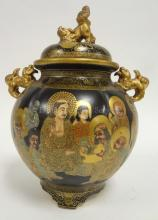 JAPANESE SATSUMA KORO; PAINTED AND GILT WITH RAKANS ON A BLACK GROUND; KARASHISHI ON SHOULDER AND FINIAL; 20TH C.; 12 IN H