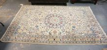 ORIENTAL RUG WITH BLUE AND RED DESIGNS ON AN IVORY GROUND. 4 FT 11 IN X 7 FT 11 IN