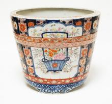 ASIAN PORCELAIN PLANTER WITH HAND DECORATED FLOWERS AND PATTERNS. HAS A HAIRLINE DOWN THE SIDE AND ACROSS THE BOTTOM. 11 1/2 INCHES TALL. 13 3/4 INCHES WIDE.