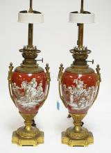 PAIR OF PORCELAIN TABLE LAMPS MOUNTED WITH BRONZE BASES AND HANDLES. DECORATED WOTH PUTTI FIGURES. 32 3/4 INCHES TALL.
