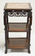 CHINESE HARDWOOD STAND 19TH C. SQUARE STAND, CARVED OPENWORK FRIEZE. ANIMAL MASKS ON CORNERS, CHAMFERED EDGES TO SHELVES INSERTS, FIGURED RED MARBLE TOP. H. 31 3/4 IN 17 3/4 IN X 17 7/8 IN. SLIGHT SHRINKAGE SEPARATION OF ONE BUTTON STRETCHERS, TINY CRACKS