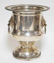 SILVER PLATED ICE BUCKET WITH RING HANDLES HELD BY LION FACES. HAS AN ENGRAVED SERPENT DECORATION ON THE FRONT. 10 INCHES TALL.