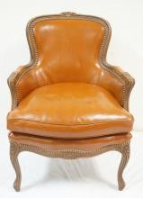 CARVED FRENCH STYLE ARM CHAIR W/ BROWN LEATHER UPHOLSTERY. 27 IN WIDE, 36 IN H
