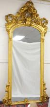 GILT ARCH TOP PIER MIRROR W/ HIGH RELIEF POPPIES AT THE CREST. 107 IN H, 48 IN WIDE.