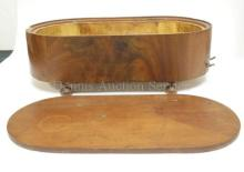 CYLINDER MUSIC BOX IN AN OVAL WOODEN CASE W/ BUN FEET. CASE IS 18 1/4 IN X 9 1/4 IN, 5 3/4 IN H